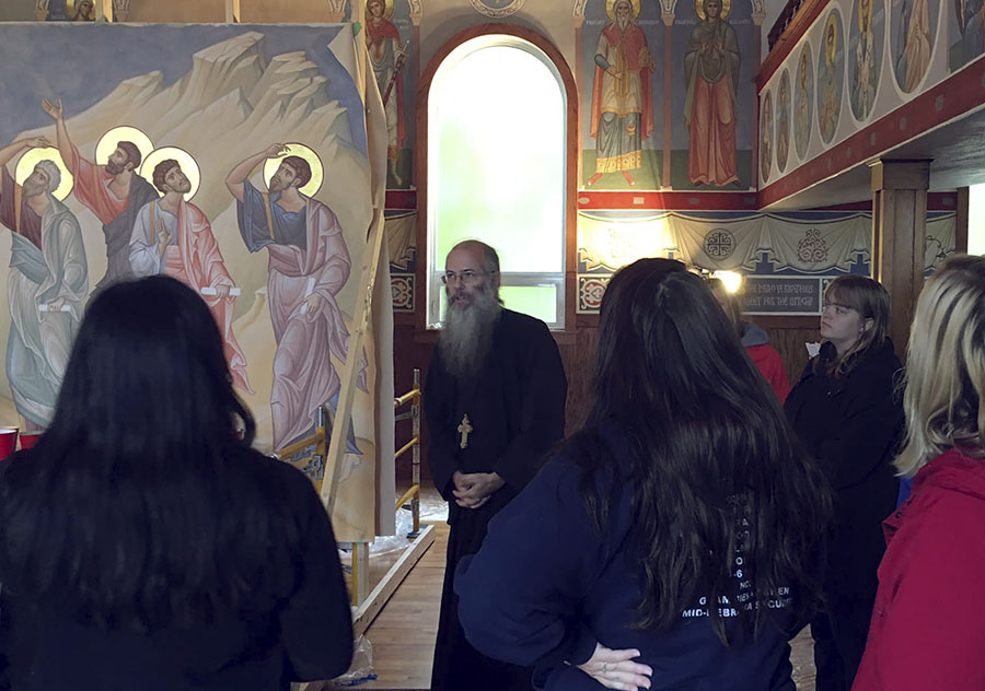 students meeting with a St. Mark's priest