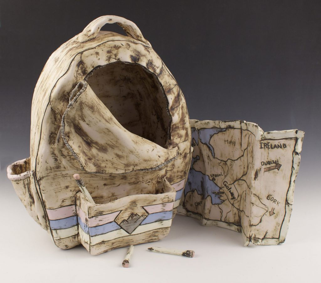 students ceramic work of backpack and map