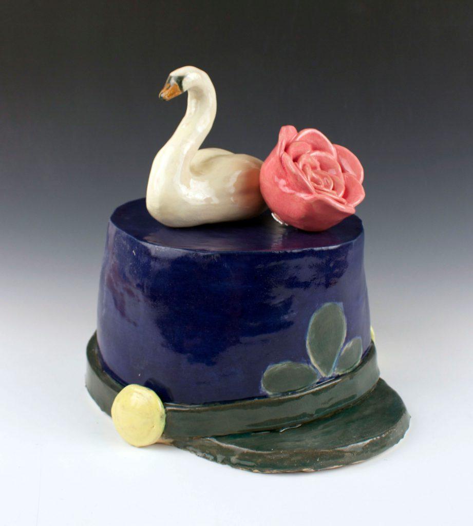 student ceramic work of swan on hat