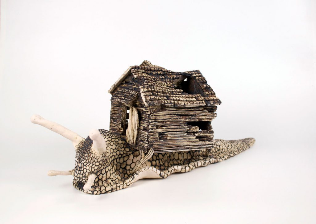 student ceramic work of snail carrying a house on its back