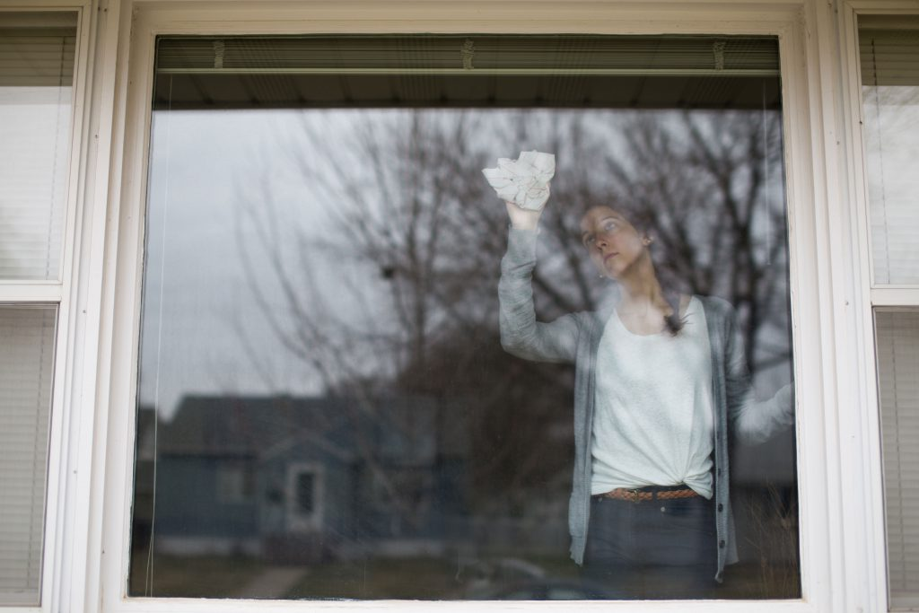 photo of a young woman cleaning a window