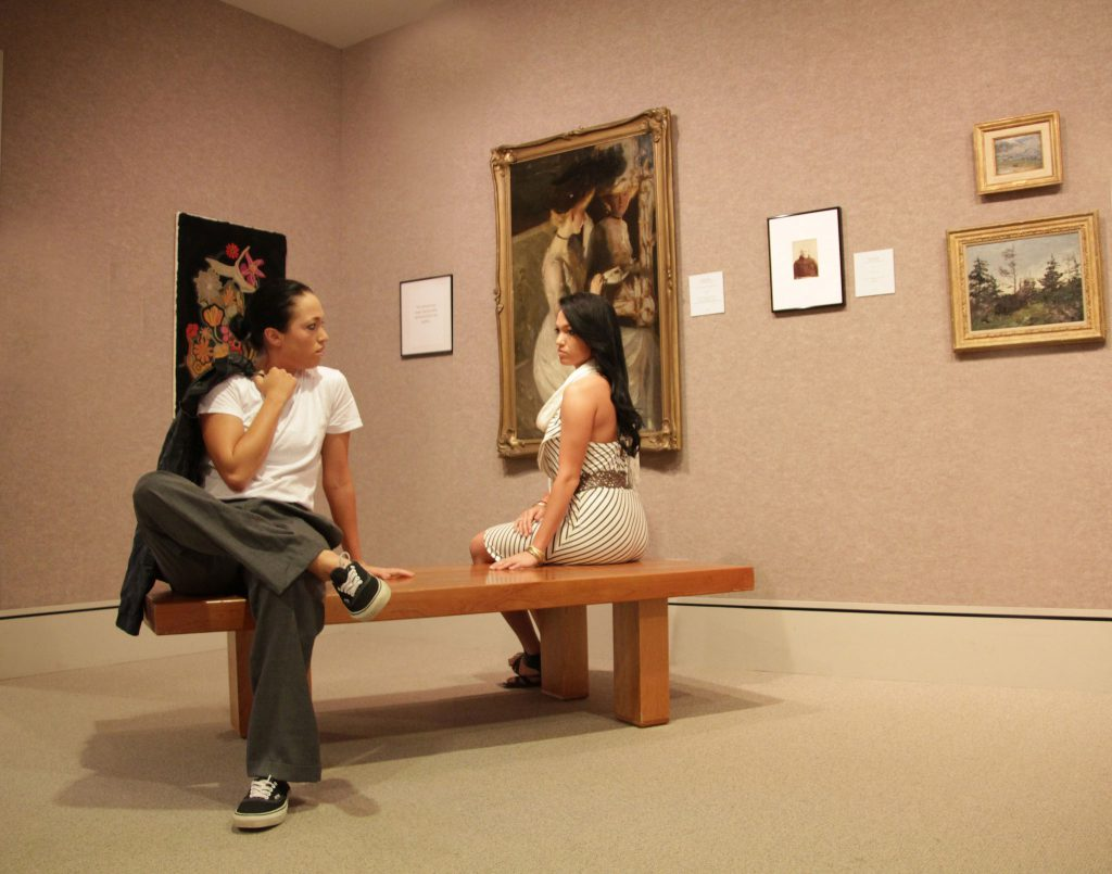 photo of two young women staring at each other in an art gallery
