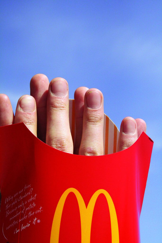 photo of hands praying through McDonald's fry box
