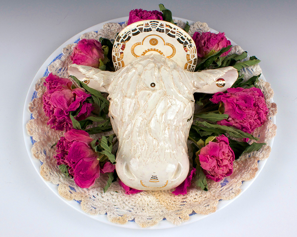 student ceramic work of sacred cow head on a plate of flowers