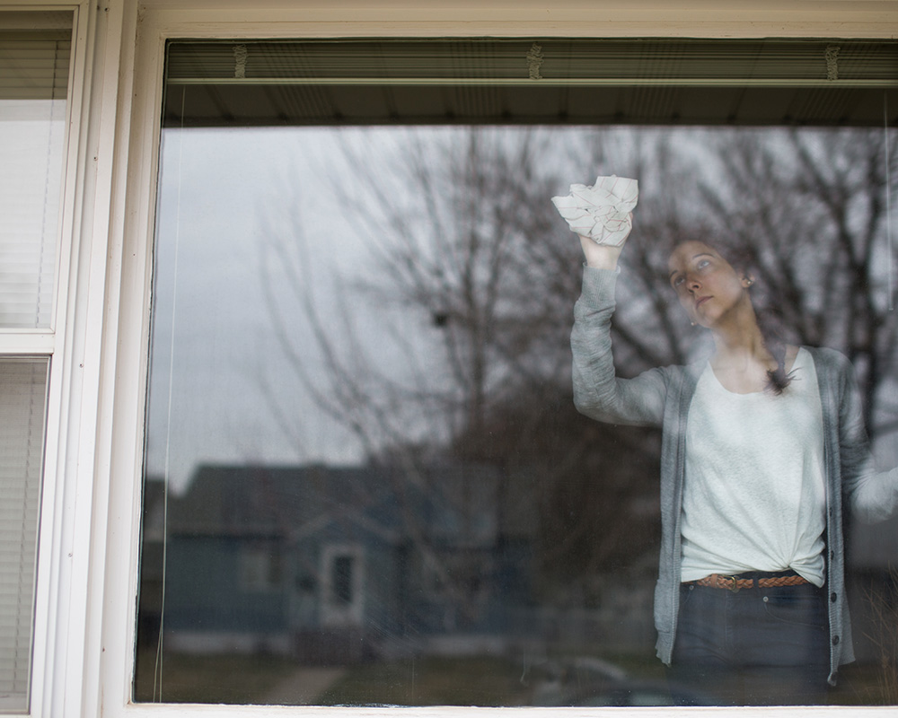 student photo of young woman cleaning a window