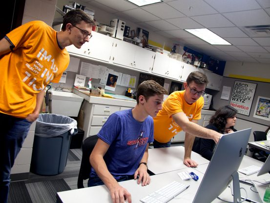 UNK students helping high school student at computer
